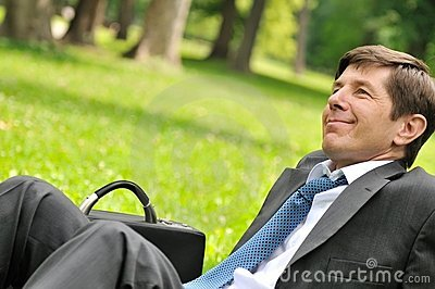 Senior business man siting in grass
