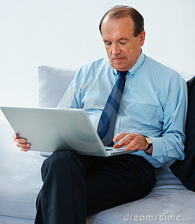 Senior business man using laptop at his home