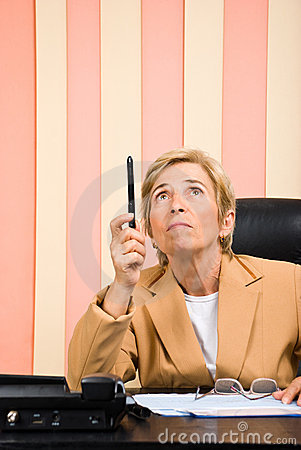 Senior business woman pointing up with pencil