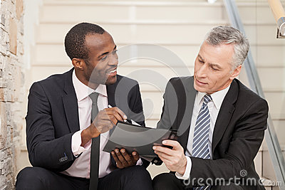 Senior businessman and mid adult businessman working together