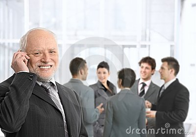 Senior businessman on phone in office lobby