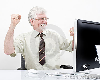 Senior businessman winning in front of computer