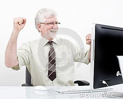 Senior businessman winning in front of computer