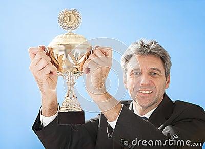 Senior businessmen holding a trophy
