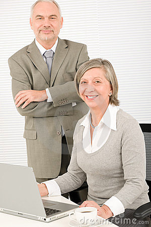 Senior businesspeople in office work on computer
