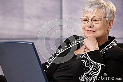 Senior businesswoman looking at computer screen