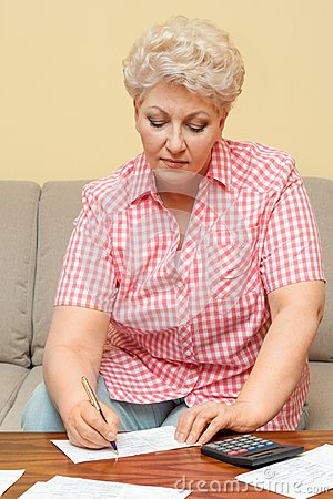 Senior calculating her debts and write