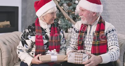 Senior Caucasian man and positive woman sitting on sofa and holding Christmas presents. Husband looking at his adorable. Wife, hugging and kissing her on cheek stock video footage