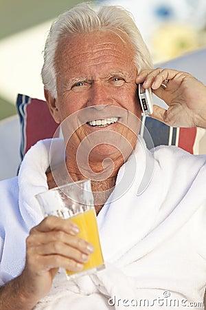 Senior on Cell Phone Drinking Orange Juice