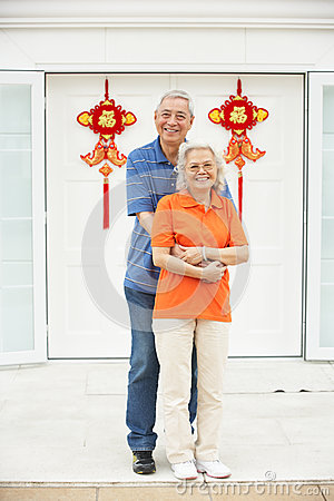 Senior Chinese Couple Outside Home With Feng Shui