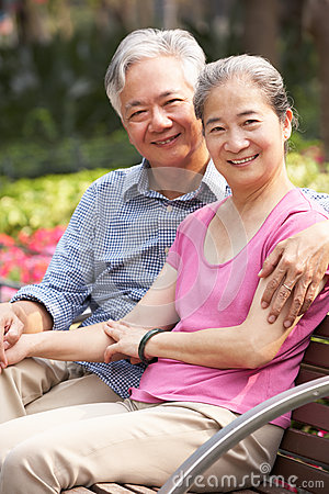 Senior Chinese Couple Relaxing On Park Bench