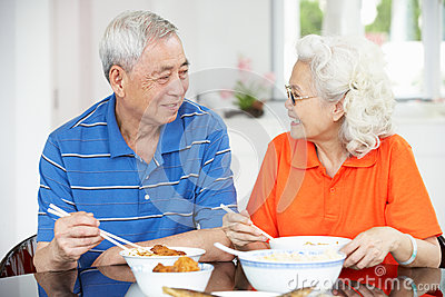 Senior Chinese Couple Sitting At Home Eating Meal