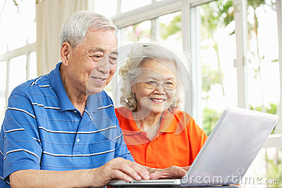 Senior Chinese Couple Using Laptop At Home