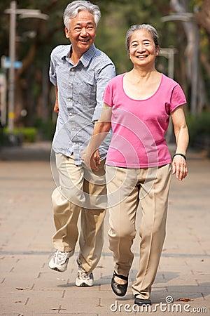 Senior Chinese Couple Walking In Park