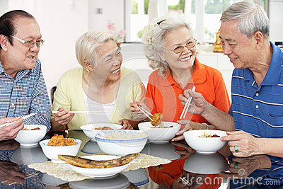 Senior Chinese Friends Eating Meal At Home