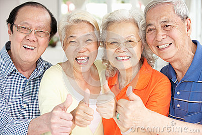 Senior Chinese Friends Relaxing On Sofa At Home