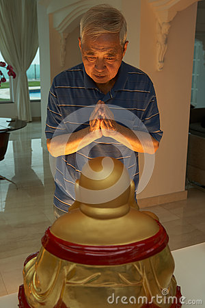 Senior Chinese Man Praying To Statue Of Buddha