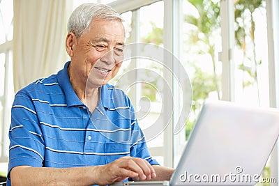 Senior Chinese Man Sitting Using Laptop At Home