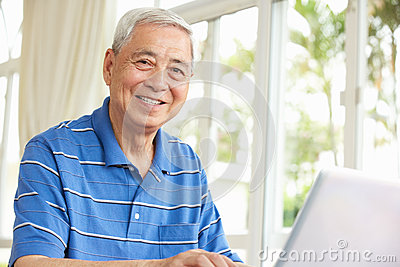 Senior Chinese Man Using A Laptop At Home