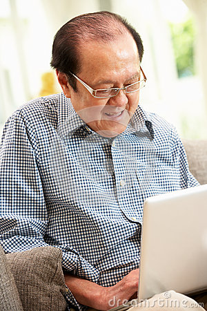 Senior Chinese Man Using Laptop Whilst Relaxing