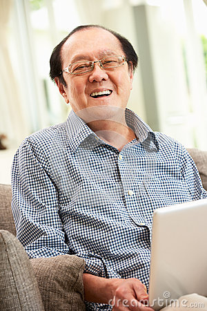 Senior Chinese Man Using Laptop Whilst Relaxing