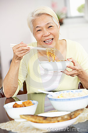 Senior Chinese Woman Sitting At Home Eating Meal