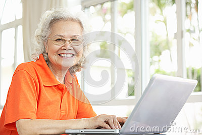 Senior Chinese Woman Using Laptop At Home