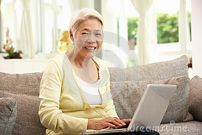 Senior Chinese Woman Using Laptop Whilst Relaxing