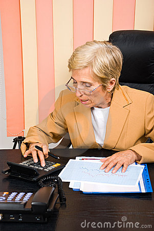 Senior corporate woman making calculations