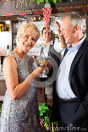 Free Senior Couple At Bar With Glass Of Wine In Hand Stock Photo - 28158400