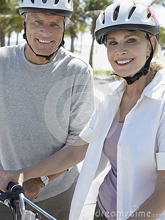 Senior Couple With Bicycles On Tropical Beach