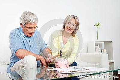 Senior couple breaking piggy bank