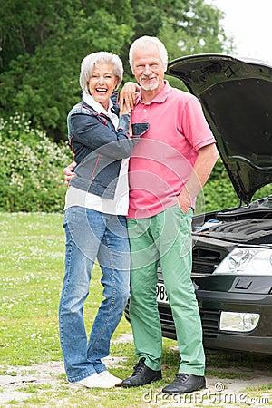 Senior couple at broken car