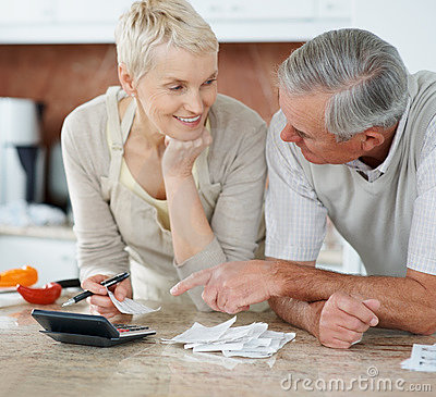 Senior couple calculating bills after shopping
