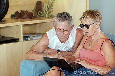 Senior couple checking laptop