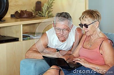 Senior couple checking laptop