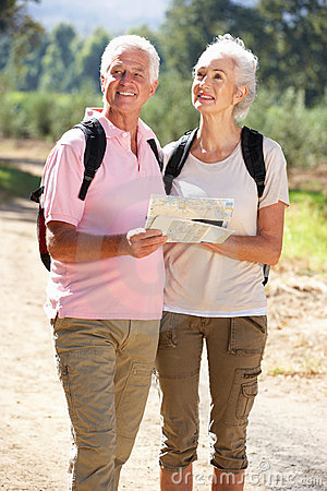 Senior couple on country walk reading map