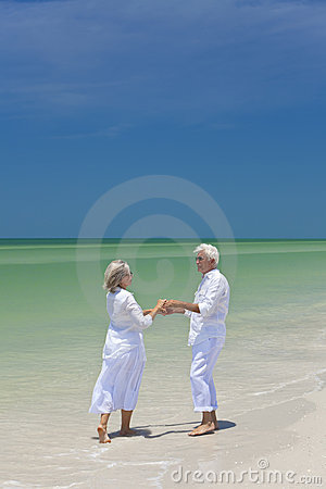 Senior Couple Dancing Holding Hands on A Beach