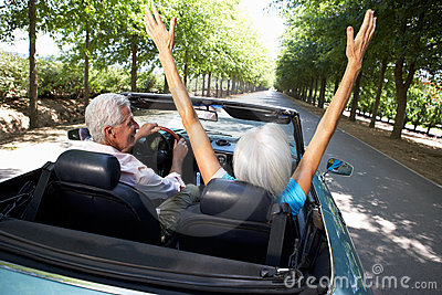 Senior couple driving in sports car