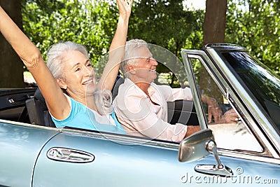 Senior couple driving sports car