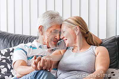 Senior couple embrace on sofa
