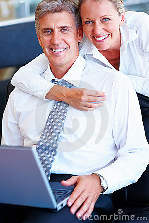 Senior couple embracing eachother while working