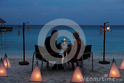 Senior Couple Enjoying Late Meal In Outdoor Restaurant