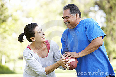 Senior Couple Exercising With American Football