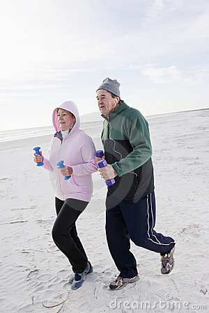 Senior couple exercising, running on beach