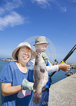 Free Senior Couple Fishing And Showing Big Grouper Fish Royalty Free Stock Images - 31338109