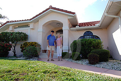 Senior couple in front of home