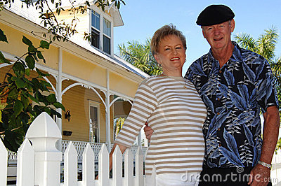 Senior couple in front of house
