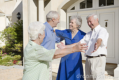 Senior couple greeting friends