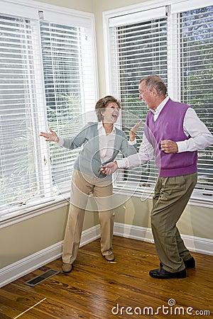 Senior couple having fun dancing in living room